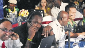 (From left) Guyana Amazon Warriors team manager Omar Khan and coach Carl Hooper consult each other, while Jamaica Tallawahs assistant coach Junior Bennett share ideas with Tallawahs owners Manish Patel and Ron Parikh during the CPL player draft at the Terra Nova Hotel in Kingston yesterday. (PHOTO: KARL MCLARTY)