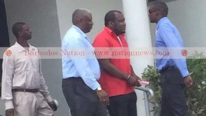 CEO of Phoenix Airways Neville Gumbs (second right) was arrested by police at his Hastings, Christ Church office yesterday. (GP)