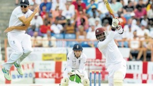 England's captain Alistair Cook (left) leaps out of the way of a Marlon Samuels drive on the first day of the second Test between West Indies and England at the National Cricket Stadium, yesterday. (PHOTO: WICB MEDIA/RANDY BROOKS)