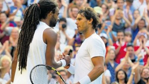 Germany's Dustin Brown (left) shakes hands with Spain's Rafael Nadal after winning their men's singles second-round match of the 2015 Wimbledon Championships at The All England Tennis Club in Wimbledon, London, England, yesterday. Brown won 7-5, 3-6, 6-4, 6-4. (PHOTOS: AFP)