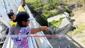 Residents looking on from the Rio Minho bridge, in May Pen, Clarendon, from which Oraine Stephenson jumped to his death Wednesday.