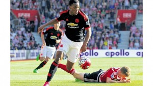 Manchester United's French striker Anthony Martial runs with the ball as Southampton's English defender Matt Targettlies is injured during their English Premier League match at St Mary's Stadium in Southampton, southern England, yesterday. Manchester won 3-2.