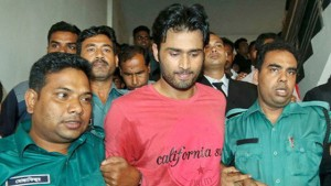 Bangladesh cricketer Shahadat Hossain (center) is led away by Bangladesh police after turning himself in on charges related to abuse.