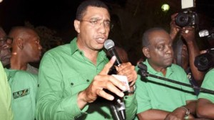 Andrew Holness delivering his victory speech to JLP supporters last night. Beside him is Derrick Smith.