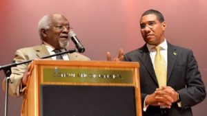 Prime Minister Andrew Holness (right), listens as Dr. Julius Garvey, son of National Hero Marcus Mosiah Garvey, addresses a town hall meeting in Queens, New York, about his late father