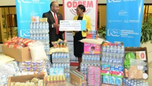 Director general of the Office of Disaster Preparedness and Emergency Management Major Clive Davis (left) receives a donation of cash and supplies from chief executive officer of National Commercial Bank Foundation Nadeen Matthews at the bank's Atrium offices in Kingston on Thursday